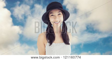 Cheerful woman with a polka dot dress and hat against road leading out to the horizon