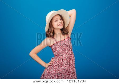 Portrait of beautiful smiling little girl in hat and sundress  standing and posing over blue background
