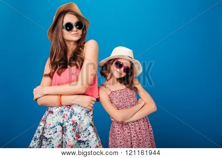 Two pretty smiling sisters standing and posing with hands folded over blue background