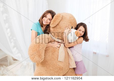 Two beautiful happy girls standing and embracing huge plush bear in children room
