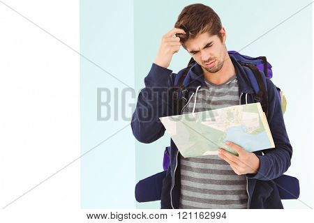 Man scratching head looking in map against bright blue