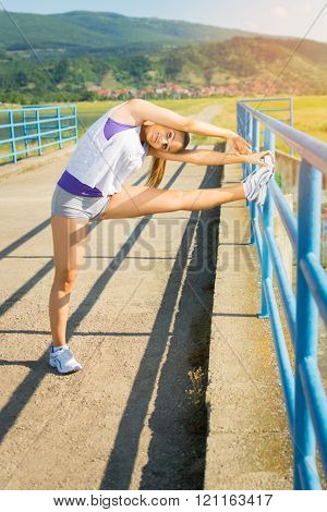 Fit young woman stretching legs after running outdoors