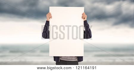 Man showing billboard in front of face against cloudy landscape background