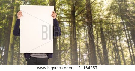 Man showing billboard in front of face against trees in a woods