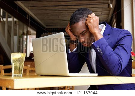 African Businessman Sitting With Laptop At Cafe