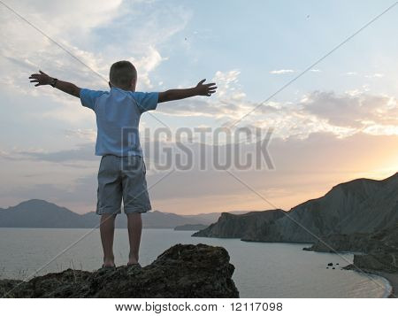boy stand on mountain top with hands up on sunset sky