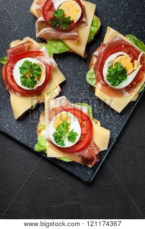 Delicious Sandwich With Prosciutto Ham, Cheese, Tomato And Egg