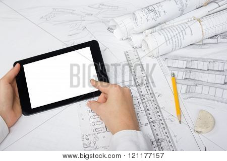 Architect working on blueprint. Architects workplace - architectural project, blueprints, ruler, blank tablet pc or smartphone. Construction concept. Engineering tools.