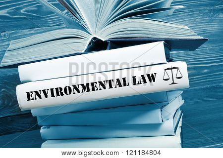 Book with Environmental Law word on table in a courtroom or enforcement office. Toned image