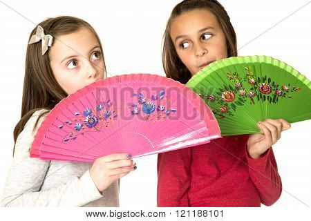 Two Preteen Girls With Fun Facial Expressions Behind Oriental Fans