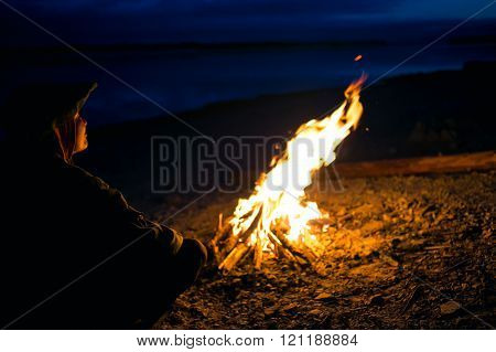 Silhouette of tourist girl around  campfire at night on the river shore.
