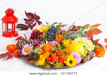 lantern with autumn decoration, flowers and fruit against a white background