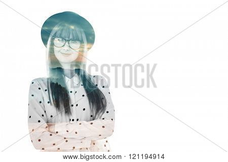 Portrait of a smiling hipster woman with arms crossed against beautiful scene of trees and mountain