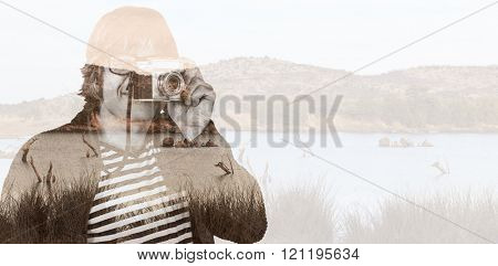 Hipster taking pictures with an old camera against lake