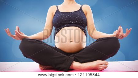 Pregnant woman sitting on mat in lotus pose against orange background