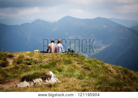 Couple of hikers admiring view and taking a rest on a peak high mountains