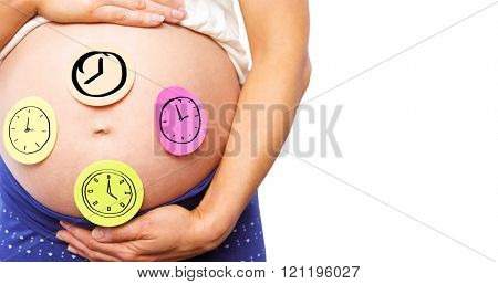 Pregnant woman with stickers on bump against clock