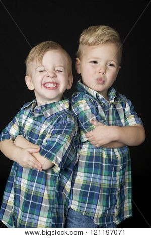 Portrait Of Two Cute Boys Standing Arms Folded Funny Expressions
