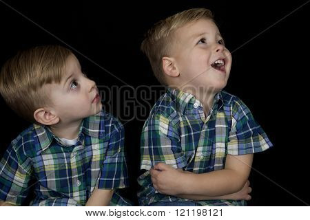 Portrait Of Two Young Boys Matching Shirts Looking Up Away From Camera