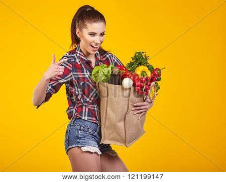 Smiling woman carrying a bag with vegetables. Yellow background.