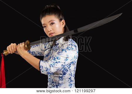 young beautiful Japanese woman looking aggressively at camera and holding sword