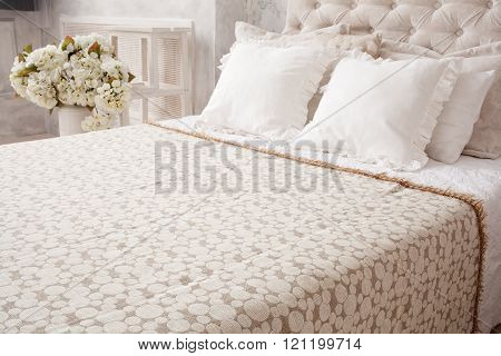 Close Up White Bed With  Bedspread And Pillows, Flowers Behind