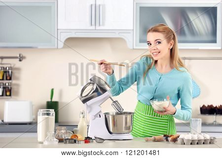 Young woman adding flour to a food processor to male a dough