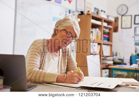 Senior female teacher at her desk marking studentsâ?? work