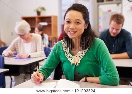 Asian woman in an adult education class looking to camera