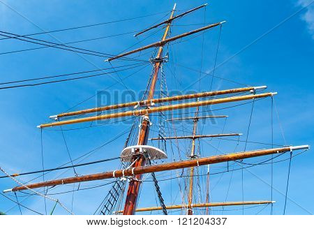Mast yacht without sails against the blue sky.