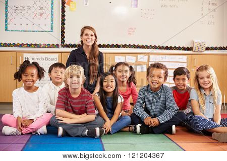 Teacher and elementary school kids sitting on classroom floor