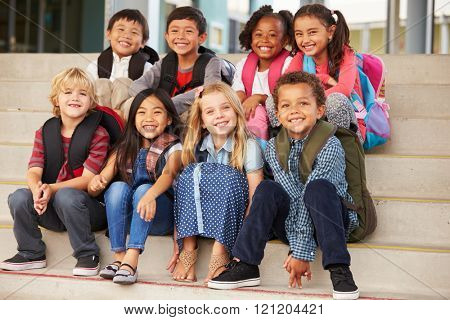 A group of elementary school kids sitting on school steps
