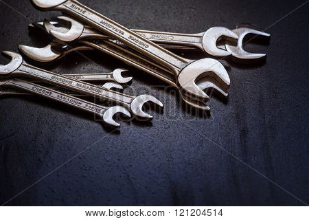 Set of the stainless steel wrench on dark background with space for text