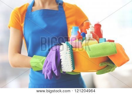 Cleaning concept. Young woman holds plastic basin with washing fluids and rags in hands, close up