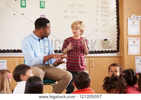 Schoolboy at the front of elementary class with teacher