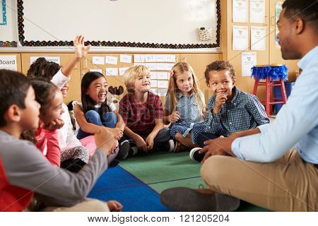 Elementary school kids and teacher sit cross legged on floor