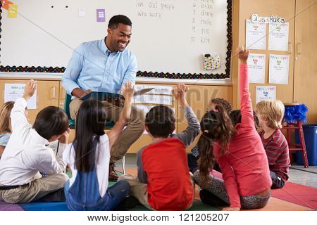 Elementary school kids sitting around teacher in a classroom