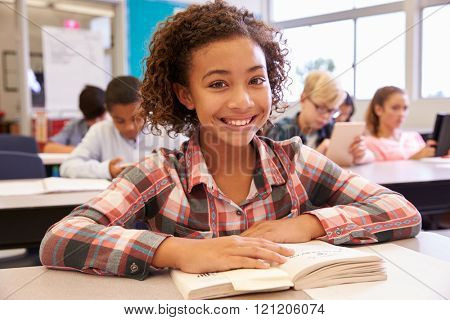 Schoolgirl at desk in elementary school looking to camera