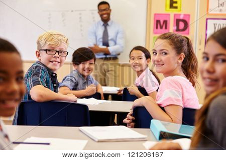 Kids at their desks in classroom turning to face the camera