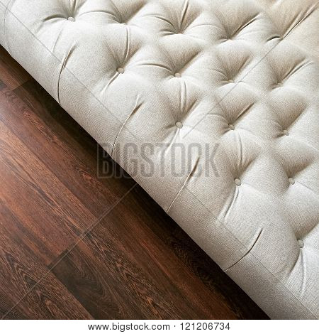 Fancy White Ottoman On Dark Wooden Floor