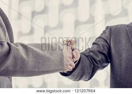 Closeup Of One Businessman Giving Money Or Bribe To The Other