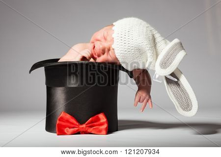 Sweet cute baby in knitted hat with a rabbit ears in the silk hat