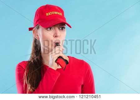 Lifeguard Woman In Cap On Duty Blowing Whistle.