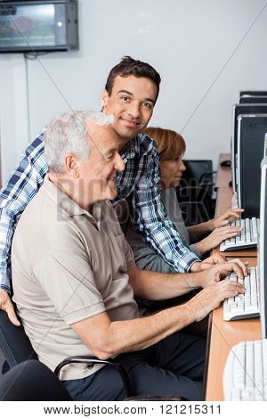 Tutor Helping Senior Man In Using Computer