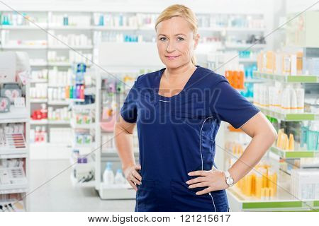 Female Chemist Standing With Hands On Hip In Pharmacy
