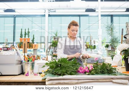Florist Cutting Stem On Rose At Counter In Flower Shop