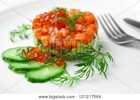 Delicious salmon tartare with red caviar on white plate