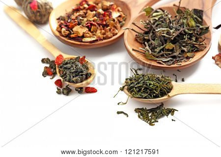 Different sorts of dry tea in wooden spoons, isolated on white
