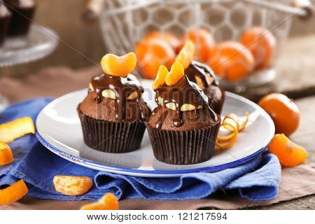 Three tasty cupcakes with slice of mandarin and chocolate on a plate over wooden background