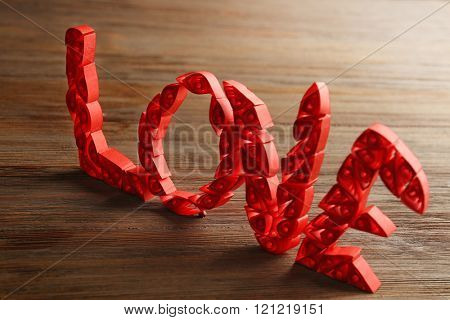 Red quilling word love on wooden background